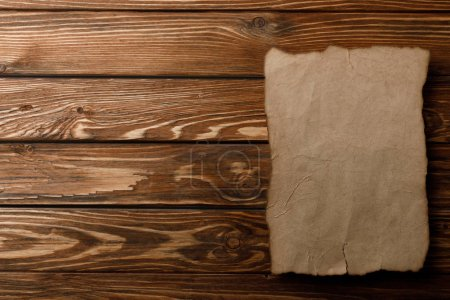 top view of aged paper sheet lying on wooden background