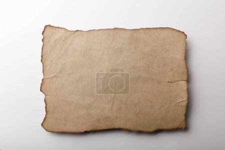 Photo for Top view of old parchment sheet lying on white background - Royalty Free Image