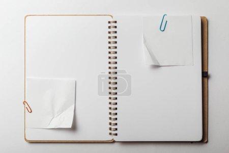 Photo pour Vue de dessus du cahier avec les pense-bêtes et les trombones sur fond blanc - image libre de droit