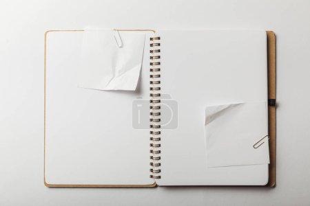 Foto de Vista superior del cuaderno con papelitos blancos y clips de papel sobre fondo blanco - Imagen libre de derechos