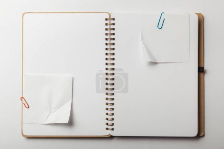 Photo for Top view of opened notebook with sticky notes and paper clips on white background - Royalty Free Image