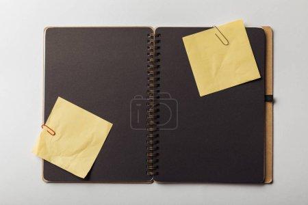 Photo pour Vue de dessus du cahier ouvert avec des feuilles noires et pense-bête avec trombones sur fond blanc - image libre de droit