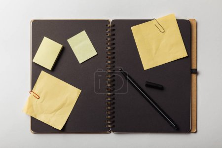 Photo for Top view of opened notebook with black sheets and yellow sticky notes with paper clips on white background - Royalty Free Image