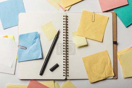 Photo for Top view of opened notebook with sticky notes with paper clips and black pen on white background - Royalty Free Image