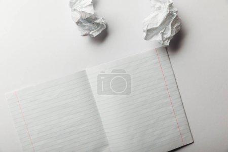 Photo pour Vue de dessus de la feuille doublée blanche située près de froissé documents sur fond blanc - image libre de droit
