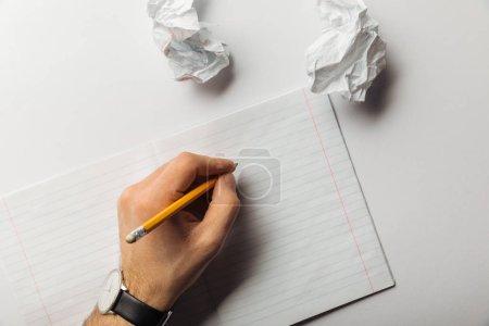 Photo pour Vue recadrée d'un homme tenant un crayon près d'une feuille doublée et des papiers froissés sur fond blanc - image libre de droit