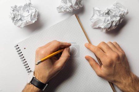 Foto de Recortada la visión del hombre escrito en hoja cuadrada en blanco cerca de papeles arrugados sobre fondo blanco - Imagen libre de derechos