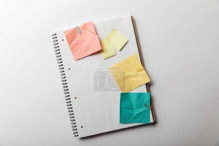 Photo pour Vue de dessus de portable avec une page blanche au carré près des notes post-it froissés sur fond blanc - image libre de droit