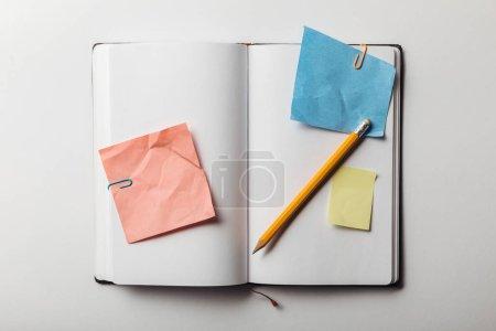 Draufsicht auf geöffnetes Notizbuch mit Haftnotizen und Büroklammern in der Nähe von Bleistift auf weißem Hintergrund