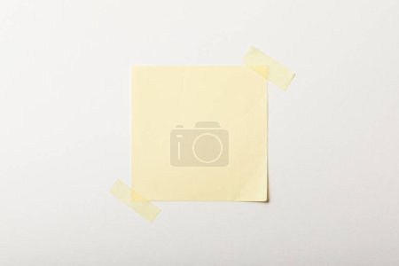 Foto de Papel en blanco amarillo con cinta adhesiva sobre fondo blanco - Imagen libre de derechos