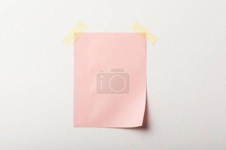 Foto de Papel en blanco rosa con cinta adhesiva sobre fondo blanco - Imagen libre de derechos