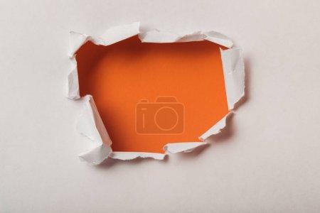 Foto de Agujero rasgado en hoja de papel sobre fondo naranja - Imagen libre de derechos