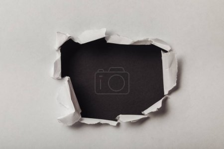 Photo for Torn hole in sheet of paper on black background - Royalty Free Image