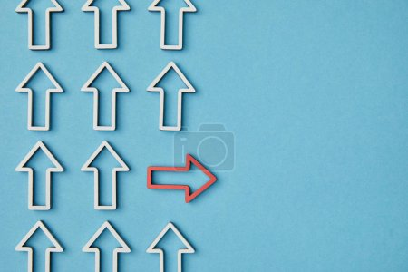 Photo for Top view of horizontal red arrow among white vertical pointers on blue background - Royalty Free Image