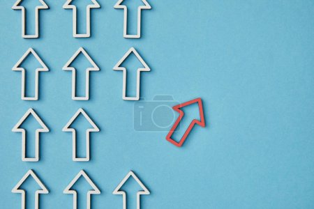 Photo for Top view of rows vertical white arrows near red pointer on blue background - Royalty Free Image