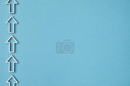 Photo for Top view of vertical row white arrows on blue background - Royalty Free Image