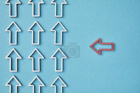Photo for Top view of horizontal red arrow pointing to vertical pointers rows on blue background - Royalty Free Image