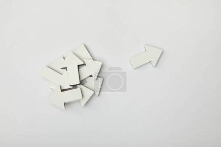 Photo for Top view of white pointer near bunch of arrows on grey background - Royalty Free Image
