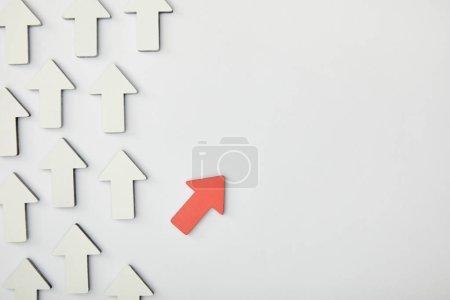 Photo pour Vue de dessus de la flèche rouge près de pointeurs blancs sur fond gris - image libre de droit