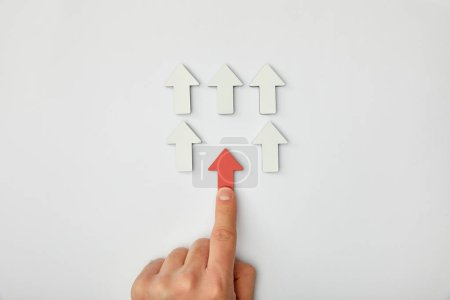Photo for Cropped view of man putting red arrow to row with white pointers on grey background - Royalty Free Image