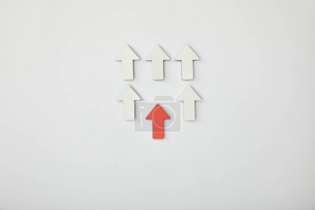 Photo for Top view of red arrow near rows with white pointers on grey background - Royalty Free Image