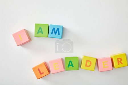 Photo pour Vue de dessus de je suis lettrage leader fait des cubes multicolores sur fond blanc - image libre de droit