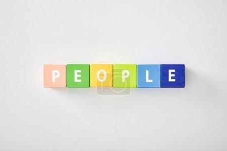 Photo pour Vue de dessus des gens lettrage fait des cubes multicolores sur fond blanc - image libre de droit