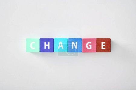 Photo pour Vue du dessus du lettrage de changement en cubes multicolores sur fond gris - image libre de droit