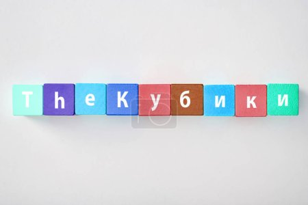 top view of the lettering made of multicolored blocks on grey background