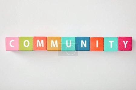 Photo pour Vue du dessus du lettrage communautaire en cubes multicolores sur fond gris - image libre de droit