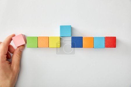 Photo for Cropped view of man laying out multicolored cubes on grey background - Royalty Free Image