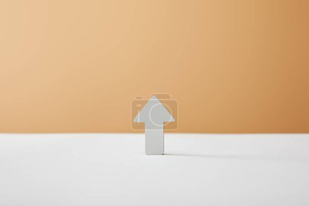 Photo for Arrow on white table and beige background - Royalty Free Image