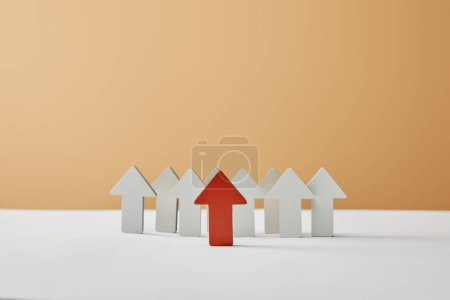 Photo for Red arrow figures with white pointing on table and beige background - Royalty Free Image