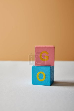 Photo for Vertical go lettering made of multicolored blocks on white table and beige background - Royalty Free Image
