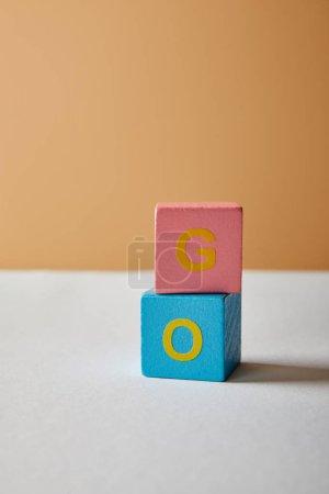 Foto de Letras de ir vertical de bloques multicolores sobre fondo beige y mesa blanca - Imagen libre de derechos