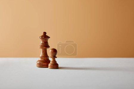 Photo pour Pièces en bois de la reine et le pion sur tableau blanc et fond beige - image libre de droit