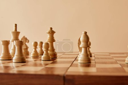 Photo for Chess on wooden chess board and beige background - Royalty Free Image