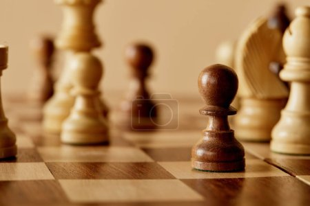 selective focus of pawn piece on wooden brown chess board and beige background