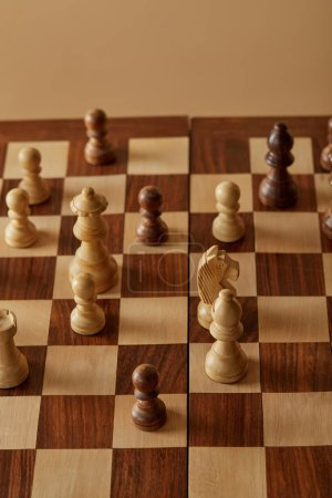 Photo for Chess pieces on wooden chess board and beige background - Royalty Free Image