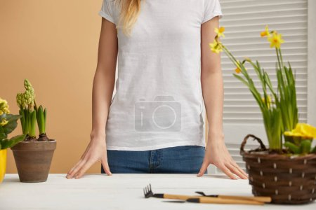 cropped view of woman standing near table with flowers and tools