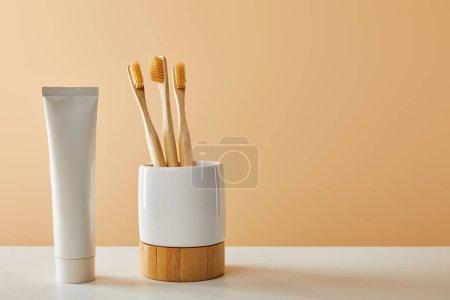 Photo pour Brosses à dents en bambou dans le support et dentifrice en tube sur table blanche et fond beige - image libre de droit