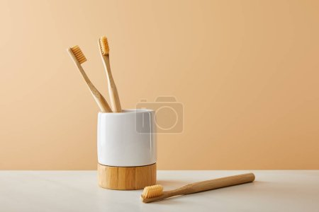 Photo for Bamboo toothbrushes and holder on white table and beige background - Royalty Free Image