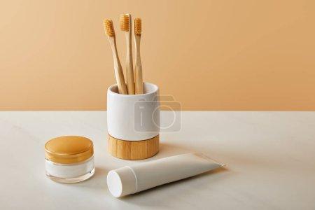 Photo pour Brosses à dents de bambou dans la titulaire, le dentifrice en tube et crème cosmétique sur tableau blanc et fond beige - image libre de droit