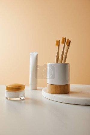 Photo pour Support avec brosses à dents sur plaque ronde en marbre, dentifrice en tube et crème cosmétique sur table blanche et fond beige - image libre de droit