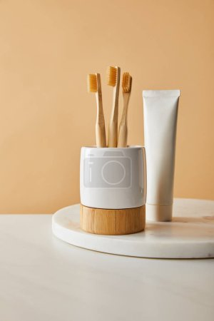 toothpaste in tube and holder with bamboo toothbrushes on white marble surface and beige background