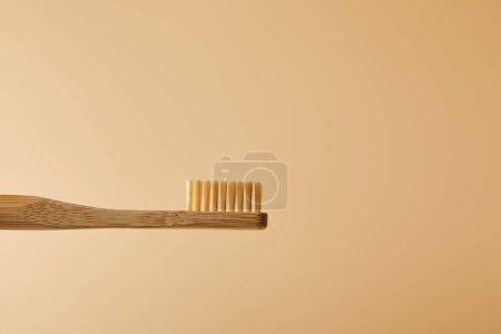 Photo pour Brosse à dents de bambou brun sur fond beige - image libre de droit