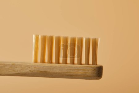 Photo for Close up view of brown bamboo toothbrush on beige background - Royalty Free Image