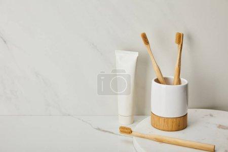 Photo pour Brosses à dents en bambou, porte et dentifrice en tube sur fond de marbre blanc - image libre de droit