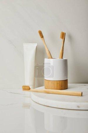 Photo pour Brosses à dents en bambou, support et dentifrice en tube sur fond de marbre blanc - image libre de droit