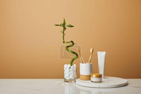 Photo pour Planche ronde avec brosses à dents dans le support, crème cosmétique et dentifrice dans le tube près de tige de bambou vert dans un vase sur fond beige - image libre de droit